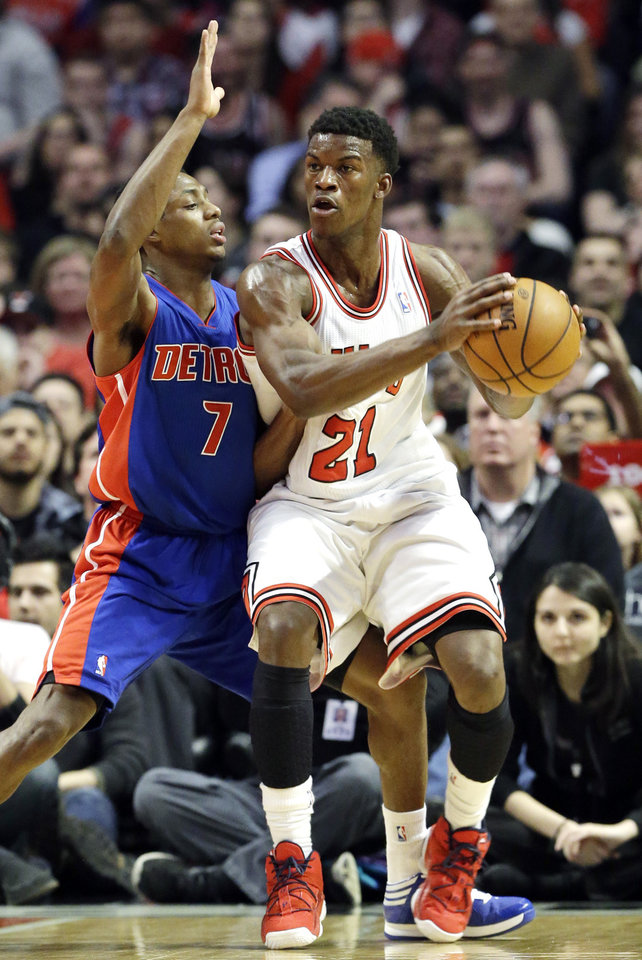 Photo - Chicago Bulls guard Jimmy Butler, right, looks to pass as Detroit Pistons guard Brandon Knight defends during the first half of an NBA basketball game in Chicago, Sunday, March 31, 2013. (AP Photo/Nam Y. Huh)
