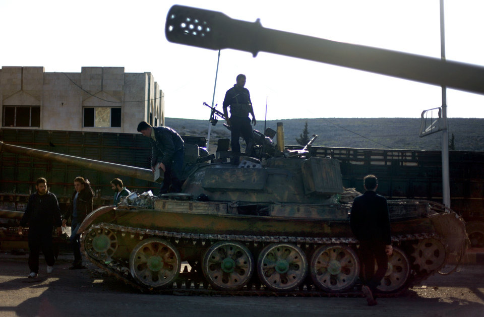 Photo - In this Monday, Nov. 19, 2012 file photo, Syrian fighters stand on a tank they took after storming a military base in Aleppo. Through mid-2012, rebel power grew and Assad's army ramped up its response. Relentless government shelling leveled neighborhoods and killed hundreds. Regular reports emerged of mass killings by the regime or thugs loyal to it, pushing more Syrians toward armed struggle. The government, which considers the opposition terrorist gangs backed by foreign powers, denied any role, and does not respond to requests for comment on its military. The rebels, too, were accused of atrocities. (AP Photo/ Khalil Hamra)