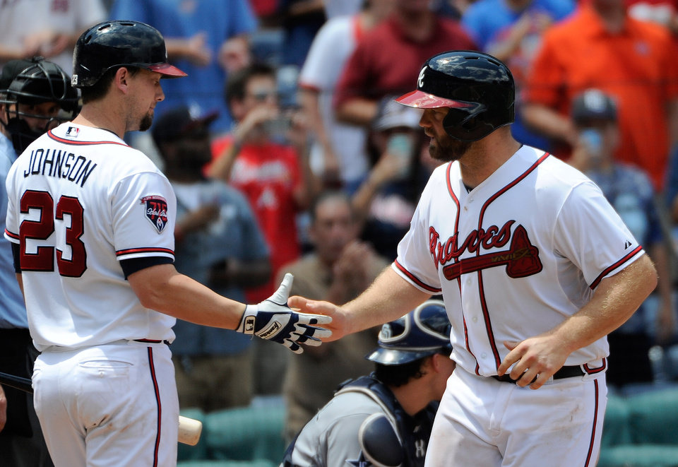 Photo - Atlanta Braves' Evan Gattis, right, is congratulated by Chris Johnson after his solo home run against the San Diego Padres during the seventh inning of a baseball game Monday, July 28, 2014, in Atlanta. (AP Photo/David Tulis)