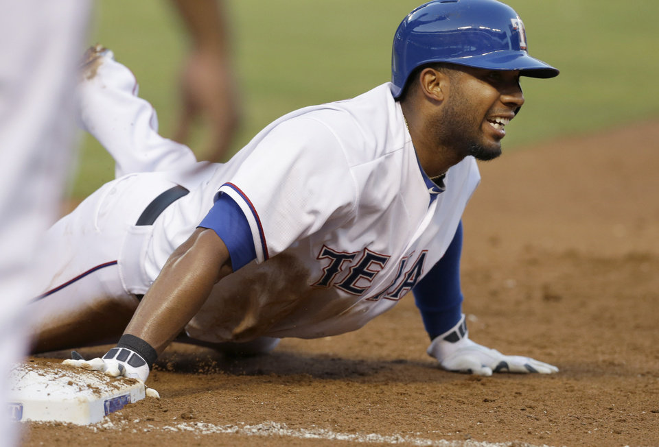 Photo - Texas Rangers Elvis Andrus dives back to touch first base beating the pick off throw during the third inning of a baseball game against the Miami Marlins in Arlington, Texas, Tuesday, June 10, 2014. (AP Photo/LM Otero)