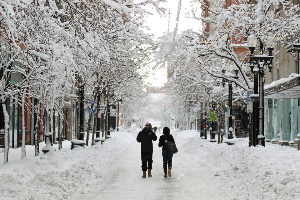 A couple walks down Westminster Street in downtown Providence, R.I., after a winter storm dumped two feet of snow on the area, Saturday, Feb. 9, 2013. (AP Photo/Stew Milne) ORG XMIT: RISM108