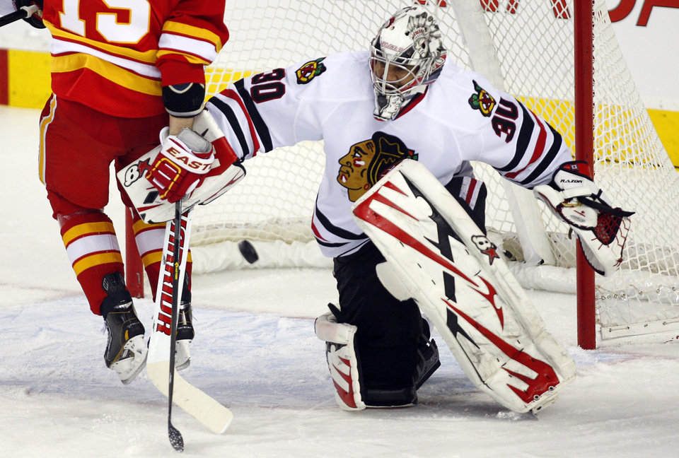 Chicago Blackhawks goalie Ray Emery, right, deflects away the puck as Calgary Flames' Tim Jackman crashes into him during the second period of an NHL hockey game in Calgary, Alberta, Saturday, Feb. 2, 2013. (AP Photo/The Canadian Press, Jeff McIntosh)