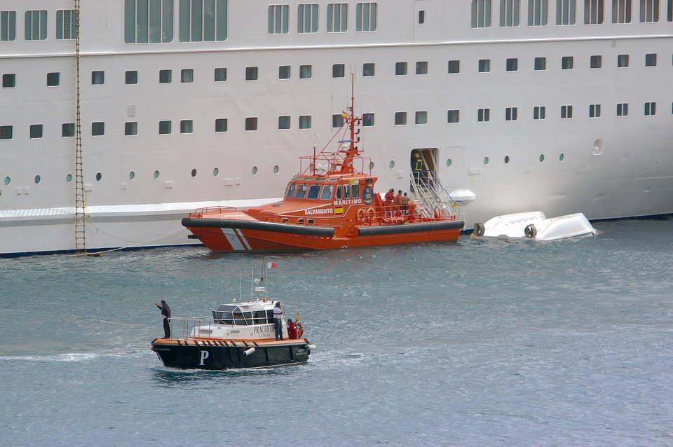 Photo - An orange rescue boat is seen docked by a capsized lifeboat from the British-operated cruise ship Thomson Majesty in Santa Cruz port of the Canary Island of La Palma, Spain, Sunday Feb. 10, 2013.  The lifeboat from the Thomson Majesty fell into the sea at port in Spain's Canary Islands, killing five people and injuring three others Sunday, officials said.  Rescue personnel were called to the dockside after a lifeboat with occupants had fallen overboard from a cruise ship. Spanish national broadcaster RTVE said an emergency training drill was taking place at the time of the accident. (AP Photo/Manuel Gonzalez)
