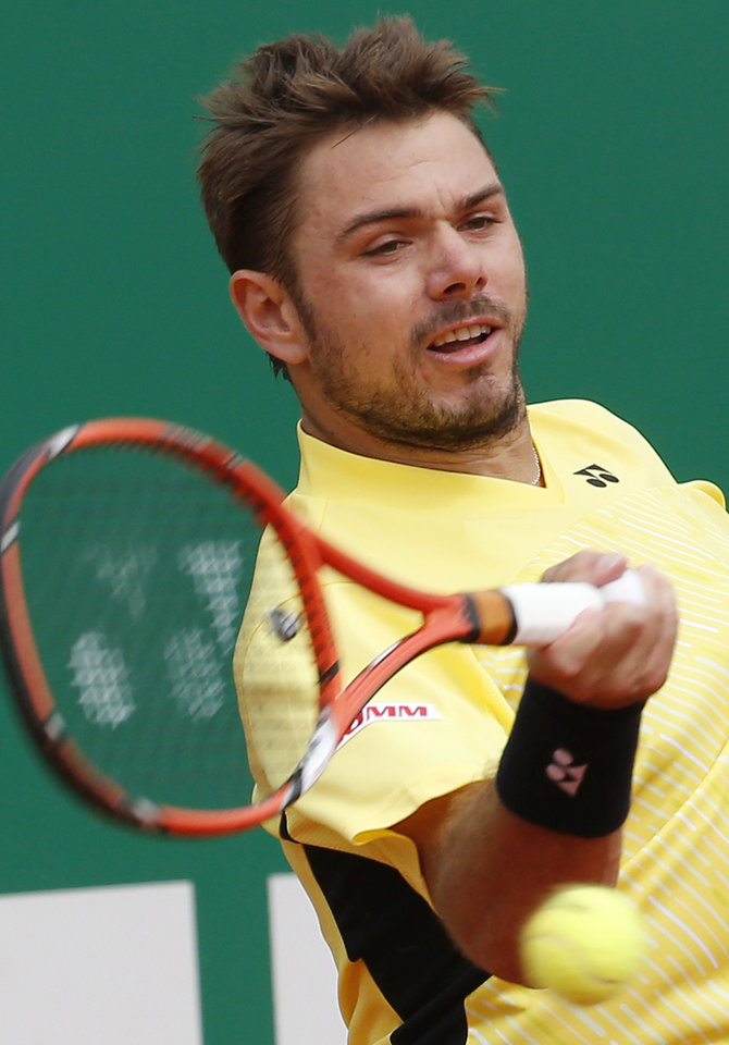 Photo - Stanislas Wawrinka of Switzerland returns to the ball to Milos Raonic of Canada during their quarterfinals match of the Monte Carlo Tennis Masters tournament in Monaco, Friday, April 18, 2014. Wawrinka won 7-6 6-2. (AP Photo/Michel Euler)