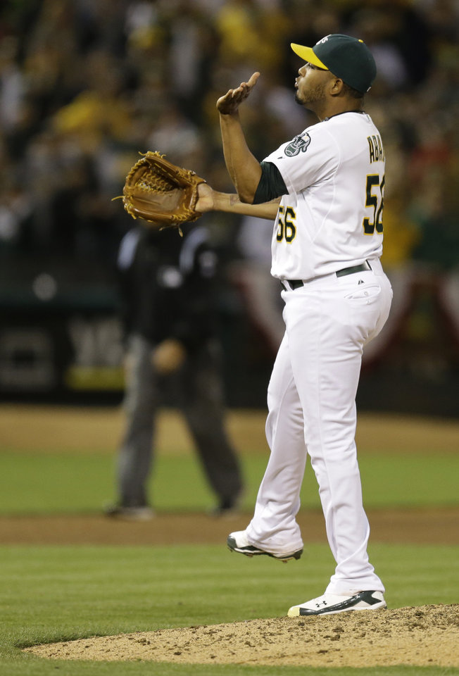 Photo - Oakland Athletics' Fernando Abad celebrates after their 5-1 win over the Toronto Blue Jays in a baseball game Saturday, July 5, 2014, in Oakland, Calif. (AP Photo/Ben Margot)