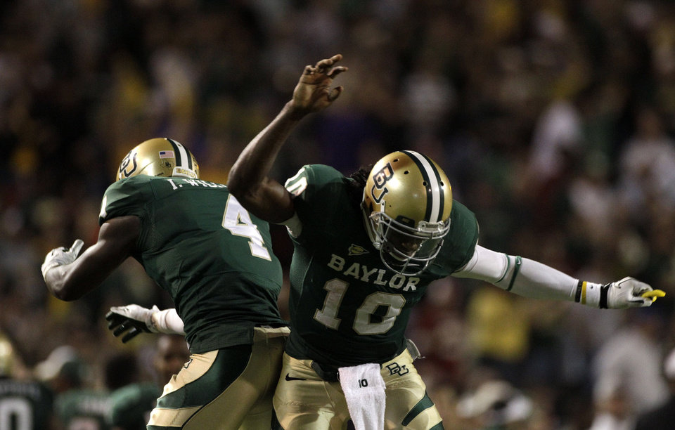 Baylor quarterback Robert Griffin III (10) and running back Isaac Williams (4) celebrate a touchdown reception by Kendall Wright in the second half of an NCAA college football game against Oklahoma, Saturday, Nov. 19, 2011, in Waco, Texas. Baylor won 45-38. (AP Photo/Tony Gutierrez) ORG XMIT: TXTG221