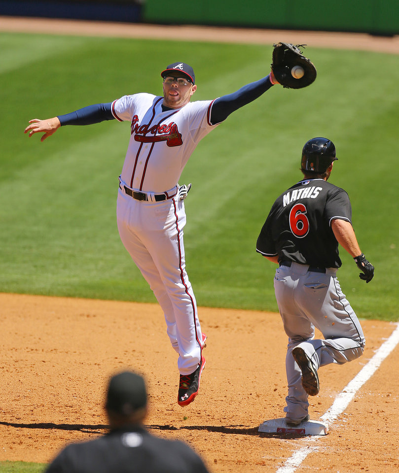 Photo - Atlanta Braves first baseman Freddie Freeman leaps to reach a throw as Miami Marlins' Jeff Mathis reaches first safely for a single during the sixth inning of a baseball game Wednesday, April 23, 2014, in Atlanta. (AP Photo/Atlanta Journal Constitution, Curtis Compton) MARIETTA DAILY OUT, GWINNETT DAILY POST OUT) LOCAL TV OUT (WXIA, WGCL, FOX 5)