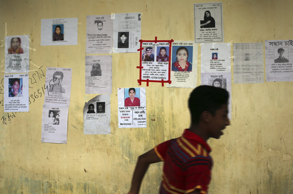 Photo - A boy runs past a school turned make-shift morgue with portraits of missing persons, mostly workers at the garment factory building which collapsed, plastered over its walls on Monday April 29, 2013 in in Savar, near Dhaka, Bangladesh. Rescue workers in Bangladesh gave up hopes of finding any more survivors in the remains of the building that collapsed five days ago, and began using heavy machinery on Monday to dislodge the rubble and look for bodies - mostly of workers in garment factories there. At least 381 people were killed when the illegally constructed, 8-story Rana Plaza collapsed in a heap on Wednesday morning along with thousands of workers in the five garment factories in the building.(AP Photo/Wong Maye-E)