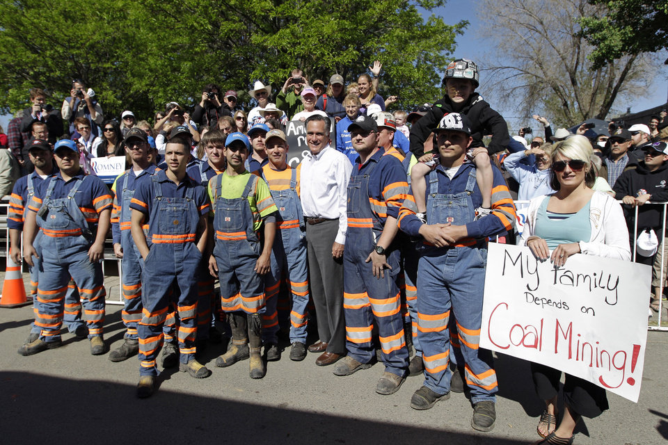 Photo -   FILE - In this May 29, 2012, file photo Republican presidential candidate, former Massachusetts Gov. Mitt Romney, poses with coal miners and their families for a photo after a campaign event in Craig, Colo. Romney has criticized President Barack Obama's treatment of coal power plants and opposes treating carbon dioxide as a pollutant and the capping of carbon dioxide emissions, but favors spending money on clean technology. He says some actions to curb emissions could hurt an already struggling economy. (AP Photo/Mary Altaffer, File)