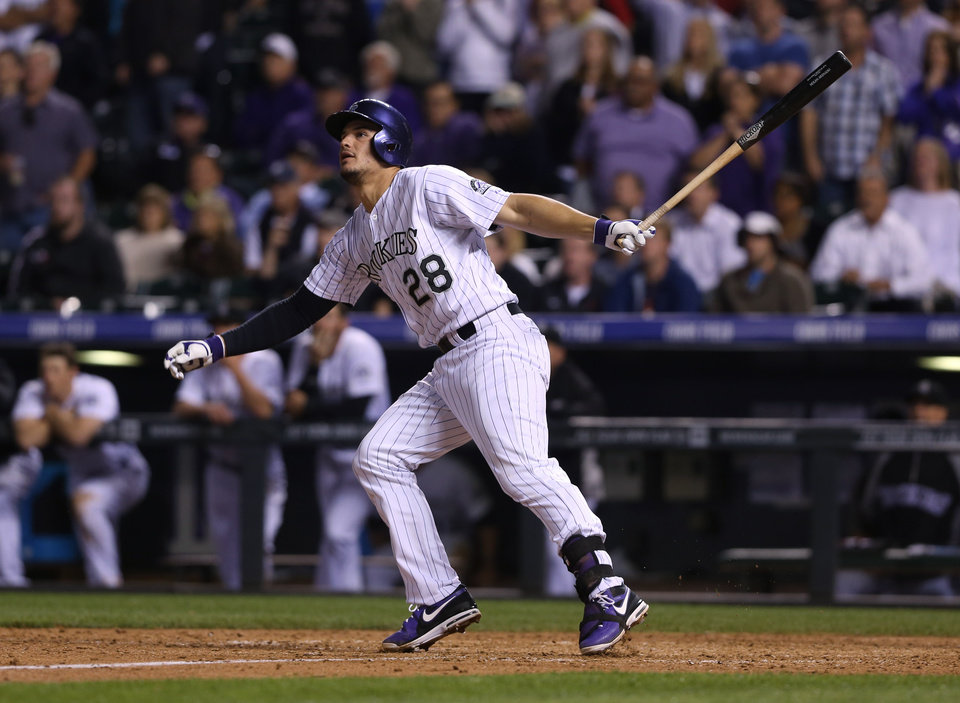 Photo - Colorado Rockies' Nolan Areando follows the flight of his walkoff double to drive in two runs against the San Francisco Giants in the ninth inning of the Rockies' 5-4 victory in a baseball game in Denver on Tuesday, May 20, 2014. (AP Photo/David Zalubowski)