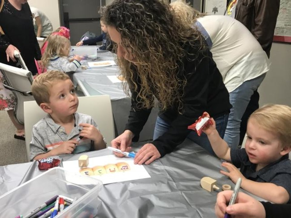 Photo -  Christina Jones helps her sons Rowen, 3  , and Barrett, 2, as they participate in activities at a Hanukkah-themed session of PJ Library hosted by the Jewish Federation of Greater Oklahoma City. [Carla Hinton/The Oklahoman]