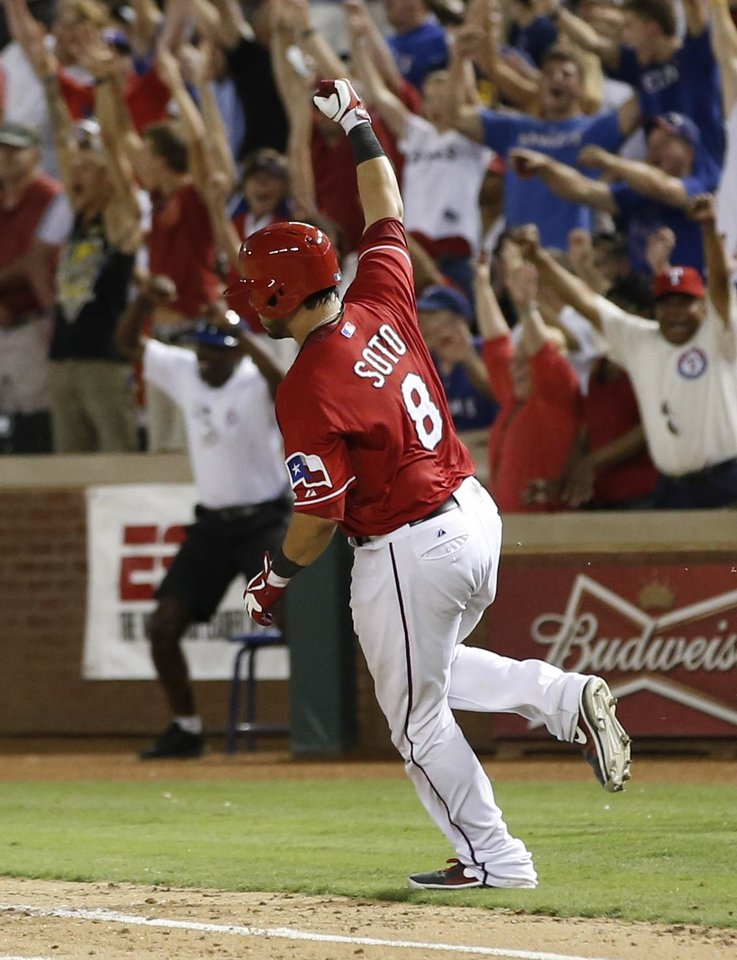 Photo - Texas Rangers' Geovany Soto rounds the bases after hitting a walk-off home run against the Los Angeles Angels during the ninth inning of a baseball game, Monday, July 29, 2013, in Arlington, Texas. The Rangers won 4-3. (AP Photo/Jim Cowsert)