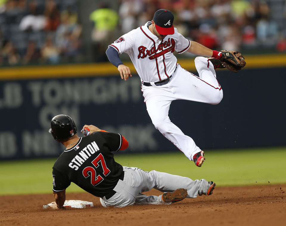 Photo - Atlanta Braves second baseman Tommy La Stella (7) avoids Miami Marlins' Giancarlo Stanton (27) as he turns a double play on a Casey McGehee  ground ball in the sixth inning of a baseball game  Thursday, July 24, 2014 in Atlanta. (AP Photo)