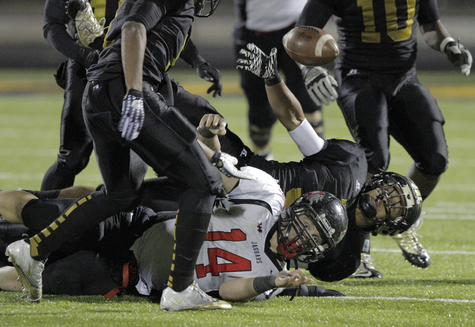 Photo - Westmoore's Josh Morgan (14) fumbles the ball during a high school football game between Midwest City and Westmoore in Midwest City, Friday, Nov. 11, 2011.  Photo by Garett Fisbeck, for The Oklahoman