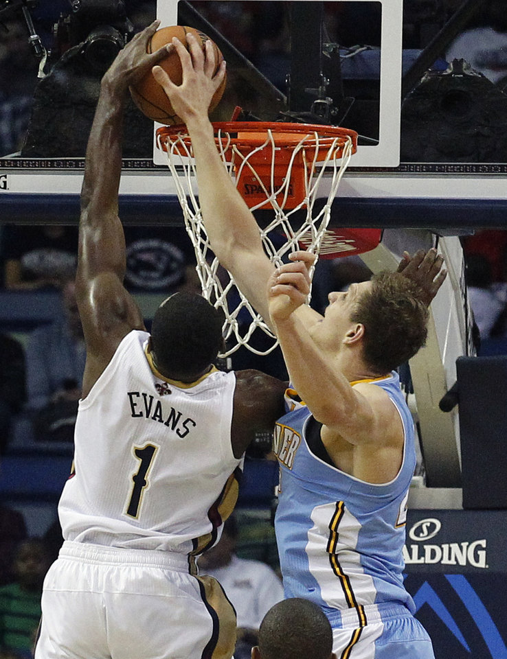Photo - New Orleans Pelicans small forward Tyreke Evans (1) goes to the basket as Denver Nuggets center Timofey Mozgov defends in the first half of an NBA basketball game in New Orleans, Sunday, March 9, 2014. (AP Photo/Bill Haber)