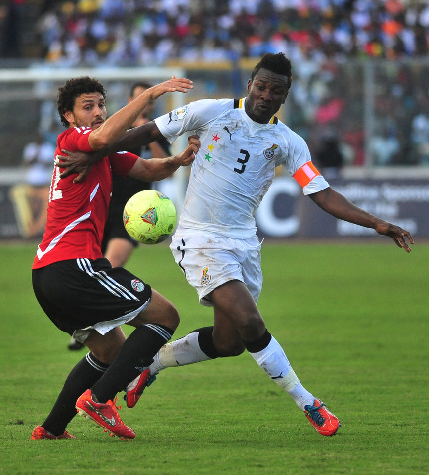 Photo - Ghana captain Asamoah Gyan, right, is challenged by Egypt's Hossam Ghaly during their World Cup playoff soccer match in Kumasi, Ghana, Tuesday, Oct. 15, 2013. Ghana stunned Egypt 6-1 in the first leg of their World Cup playoff on Tuesday, with Gyan's fifth-minute goal kicking off a dominant performance that makes the Black Stars overwhelming favorites to be one of the five African teams in Brazil next year. (AP Photo)