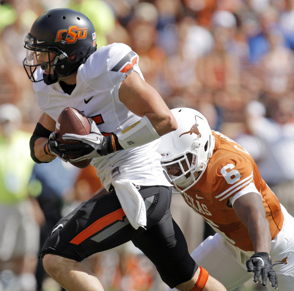 Photo - Oklahoma State's Josh Cooper (25) makes a long catch in front of Texas' Christian Scott (6) in the first quarter during a college football game between the Oklahoma State University Cowboys (OSU) and the University of Texas Longhorns (UT) at Darrell K Royal-Texas Memorial Stadium in Austin, Texas, Saturday, Oct. 15, 2011. Photo by Nate Billings, The Oklahoman