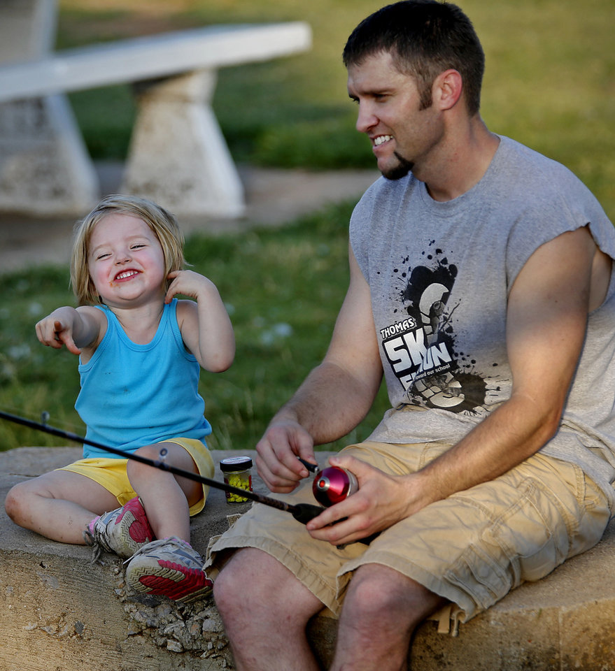 Ezra Zoschke enjoys a laugh with his daughter Brinley as they do some fishing Wednesday at the Yukon City Park. <strong>CHRIS LANDSBERGER - CHRIS LANDSBERGER</strong>