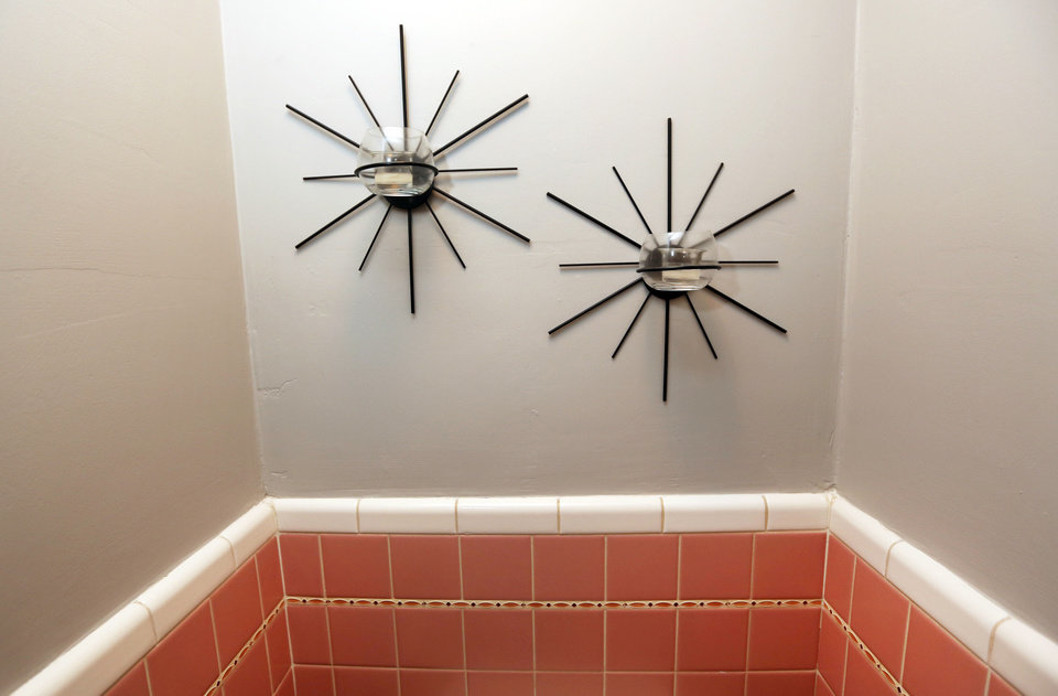 Photo - Wall-mounted bathroom candle holders fit the midcentury design of Mike and Lindsey Deatsch's home.  Steve Gooch - The Oklahoman
