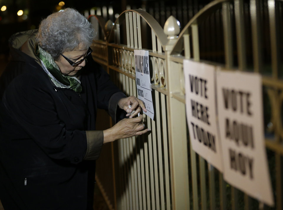Photo - A polling place worker hangs signs before the start of a special election for the vacant New Jersey seat in the U.S. Senate, Wednesday, Oct. 16, 2013, in Newark, N.J. Democrat Cory Booker is going up against Republican Steve Lonegan. (AP Photo/Julio Cortez)