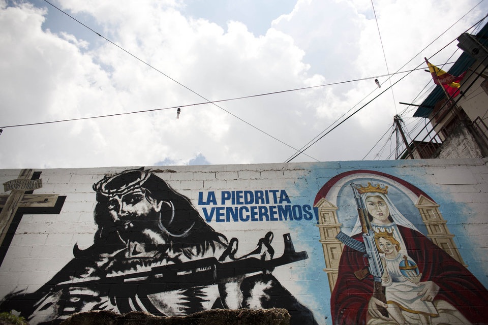 Photo -   In this Sept. 16, 2010, a mural depicts an image of Jesus Christ holding a machine, left, and an image of the Virgin Mary holding a young Jesus and a machine gun on a wall in La Piedrita or Little Rock neighborhood gang turf in Caracas, Venezuela. Heavily armed gangs that pledge allegiance to President Hugo Chavez rule over fiefdoms in slums where police rarely patrol, employing vigilante justice and collecting extortion money. A shooting attack on the opposition candidate's entourage has kindled worries that Chavez's defenders could resort to violence if cancer impedes his bid for re-election. The gangs, however, are loosely organized and do not appear to be taking orders from the government. (AP Photo/Ariana Cubillos)
