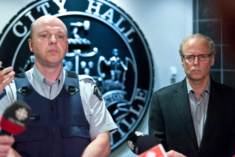 Photo - Royal Canadian Mounted Police officer Damien Theriault and Mayor George LeBlanc pause to collect themselves before addressing the media during a late night news conference at City Hall in Moncton,  New Brunswick  on Wednesday June 4, 2014. Three police officers were shot dead and two others injured in a rare case of gun violence in the east coast Canadian province of New Brunswick, officials said. (AP Photo/The Canadian Press, Marc Grandmaison)