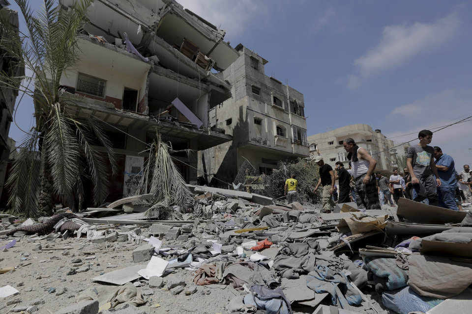 Photo - Palestinian relatives salvage belongings from the rubble of a three-story building belonging to the Abdul Hadi family damaged after an Israeli strike in Gaza City in the northern Gaza Strip, Sunday, Aug. 24, 2014. (AP Photo/Adel Hana)