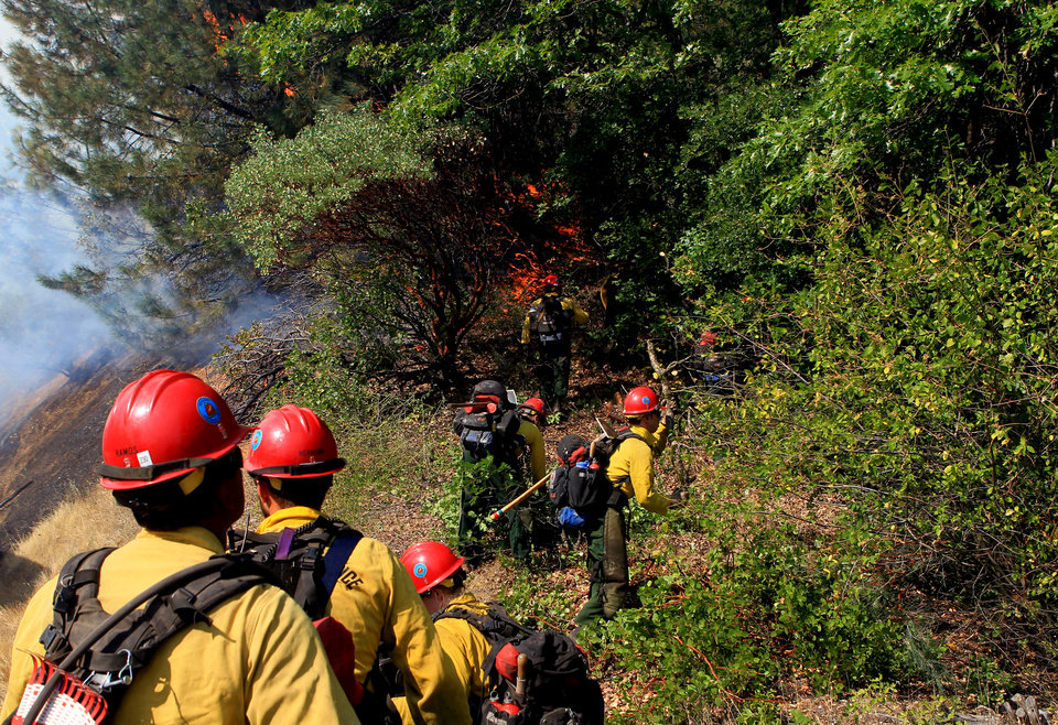 U.S. Forest Service firefighters cut down brush while they work to put out the Salt Creek Fire Wednesday, Aug. 1, 2012, along the northbound side of Interstate 5 in Shasta County, Calif. AP photo