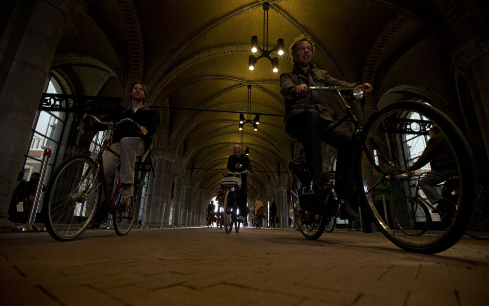 Photo - Bicycles pass through the reopened bike path under Rijksmuseum in Amsterdam Monday May 13, 2013. Hundreds of bicycles pedaled triumphantly through Rijksmuseum,  signaling the end of more than a decade of efforts by cyclists to ensure a passageway that runs under and through the Rijksmuseum would remain open to bike traffic. The museum, which houses masterpieces by Rembrandt van Rijn and Vincent van Gogh, among others, opened last month after a 10-year renovation. Architects and successive museum directors had opposed allowing bikes through, and a local government tried to have them barred on safety grounds. But in a city that has more bicycles than people, the bike lobby prevailed. (AP Photo/Peter Dejong)