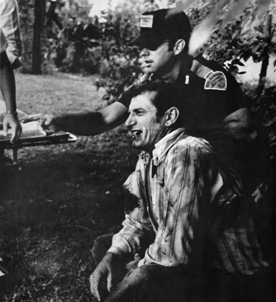 Oklahoma Highway Patrol Lt. Hoyt Hughes cries in pain as a fellow patrolman signals for aid. Hughes was wounded in the shoulder after he was involved in a gun battle with two escapees from the Oklahoma State Penitentiary on May 26, 1978. Copy of an AP transmission from The Oklahoman Archive, Tuesday, Dec. 6, 2011.