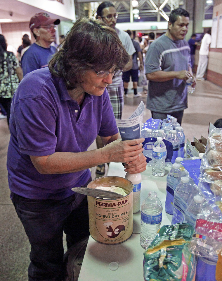 Photo - Volunteer nurse Ronda Kelso, of Phoenix, mixes powder milk for immigrants waiting at at the Greyhound bus terminal, Thursday, May 29, 2014 in Phoenix. About 400 mostly Central American women and children caught crossing from Mexico into south Texas were flown to Arizona this weekend after border agents there ran out of space and resources.  Officials then dropped hundreds of them off at Phoenix and Tucson Greyhound stations, overwhelming the stations and humanitarian groups who were trying to help. (AP Photo/Rick Scuteri)