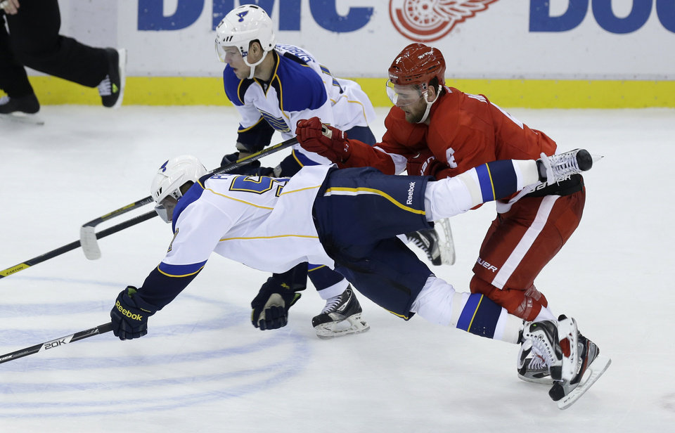St. Louis Blues left wing David Perron (57) falls in front of Detroit Red Wings defenseman Jakub Kindl (4), of the Czech Republic, during the second period of an NHL hockey game in Detroit, Friday, Feb. 1, 2013. (AP Photo/Carlos Osorio)
