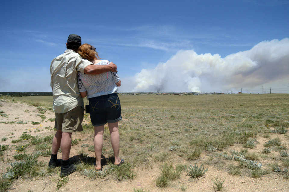 Photo - Dave and Linda Burgess watch as a plume rises near their home on Burgess Road in The Black Forest on Wednesday, June 12, 2013 near Colorado Springs, Colo. They were not sure if their home survived the fire.  Three Colorado wildfires fueled by hot temperatures, gusty winds and thick, bone-dry forests have together burned dozens of homes and led to the evacuation of more than 7,000 residents and nearly 1,000 inmates at medium-security prison. (AP Photo/Bryan Oller)