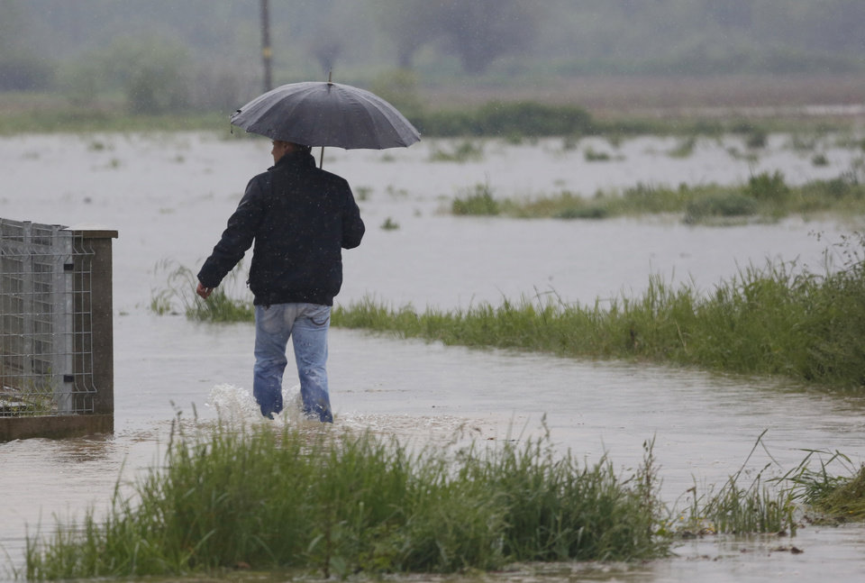 Photo - A man walks through a flooded street in a suburb of Sarajevo on Wednesday, May 14, 2014. Heavy rainfall caused the river Bosna to flood surrounding areas causing power cuts and road blockades in some suburban and rural areas. (AP Photo/Amel Emric)