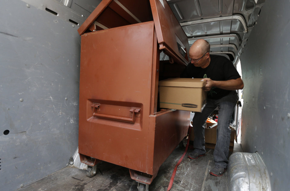 Photo - Phil Tobias, director of Sea of Green Farms, loads boxes of recreational marijuana into a lockbox inside a van, Tuesday, July 8, 2014, in Seattle, for delivery to a store in Bellingham, Wash. It was the first delivery for the company since retail licenses were issued by the state on Monday. (AP Photo/Ted S. Warren)