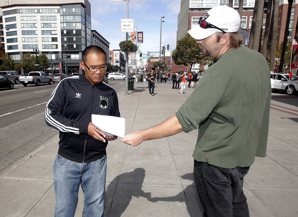 Bradley Meadows, right, friend of Los Angeles Dodgers fan Jonathan Denver, passes out a flier to Roger Manuel, left, outside AT&T Park before the Giants' baseball game in San Francisco, Sunday, Sept. 29, 2013. Denver, 24, was fatally stabbed Wednesday during a melee following a Dodgers-Giants game. (AP Photo/Tony Avelar)