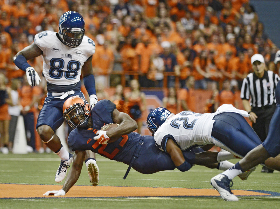 Photo - Syracuse's Devante McFarlane, center, gets tackled by Villanova's Jerry Miles during an NCAA college football game at the Carrier Dome, Friday, Aug. 29, 2014 in Syracuse, N.Y. (AP Photo/Heather Ainsworth)