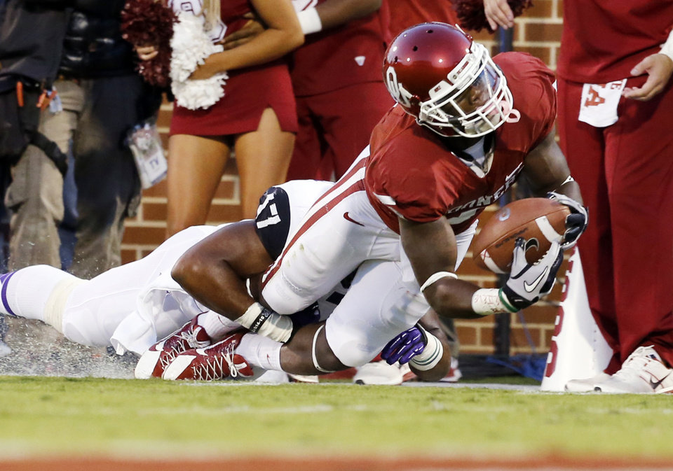 Photo - Oklahoma's Durron Neal (5) stretches for extra yardage as he is tackled by TCU's Sam Carter (17) during a college football game between the University of Oklahoma Sooners (OU) and the TCU Horned Frogs at Gaylord Family-Oklahoma Memorial Stadium in Norman, Okla., on Saturday, Oct. 5, 2013. Photo by Steve Sisney, The Oklahoman