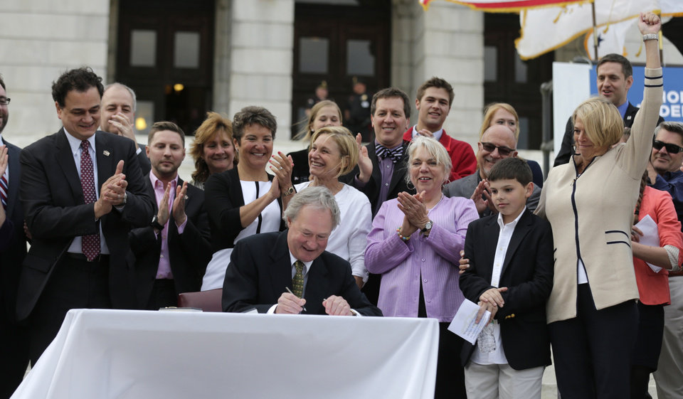 Photo - Rhode Island Gov. Lincoln Chafee signs a gay marriage bill into law outside the State House in Providence, R.I., Thursday, May 2, 2013. (AP Photo/Charles Krupa)