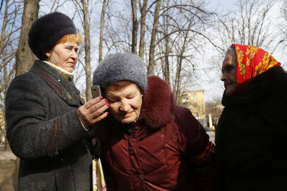 Photo - In this photo taken Tuesday, March 11, 2014, women listen to a statement given earlier in the day by Ukrainian President Viktor Yanukovich from Rostov-on-Don, Russia in Luhansk, eastern Ukraine. The pro-Moscow president fled office last month after prolonged street protests and bloodshed in Kiev, and was succeeded by a government made up of politicians friendlier to the United States and European Union. (AP Photo/Sergei Grits)