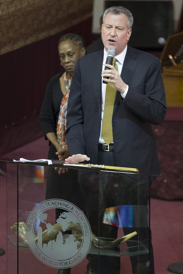 Photo - New York City Mayor Bill de Blasio speaks alongside his wife Chirlane McCray during Sunday services at the Bethel Gospel Assembly as the congregation mourns the deaths of two members in Wednesday's explosions in the East Harlem neighborhood of New York, Sunday, March 16, 2014. De Blasio said the women lost