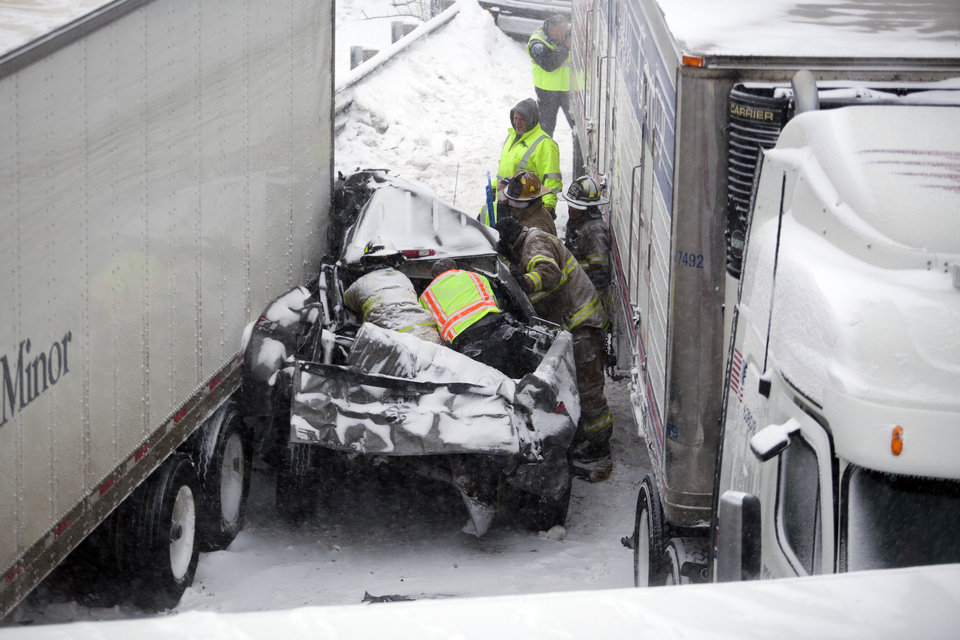 Photo - Rescue workers attempt to free a man trapped in a truck on Wednesday, Feb. 5, 2014 on I-94 near the Elm Street bridge in Jackson, Mich. Several multi-vehicle crashes, including some with injuries, were reported along Interstate 94 in the Jackson area. (AP Photo/MLive.com, Michelle Tessier) LOCAL TV OUT; LOCAL INTERNET OUT