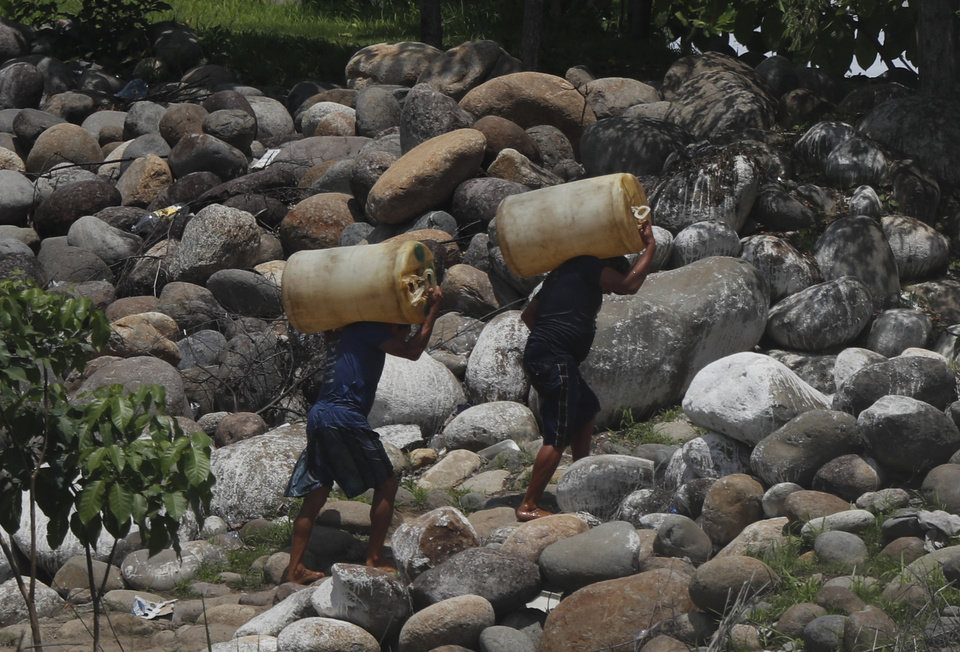 Photo -  Men carry containers of black-market gasoline, recently brought illegally across the Suchiate River on rafts, near Ciudad Hidalgo, Mexico, Thursday, June 6, 2019. U.S. President Donald Trump has pledged to impose 5% tariffs on Mexican products unless Mexico country prevents Central American migrants from traveling through its territory. Some migrants pay raft operators in order to avoid swimming or going through the official border crossing. (AP Photo/Marco Ugarte)