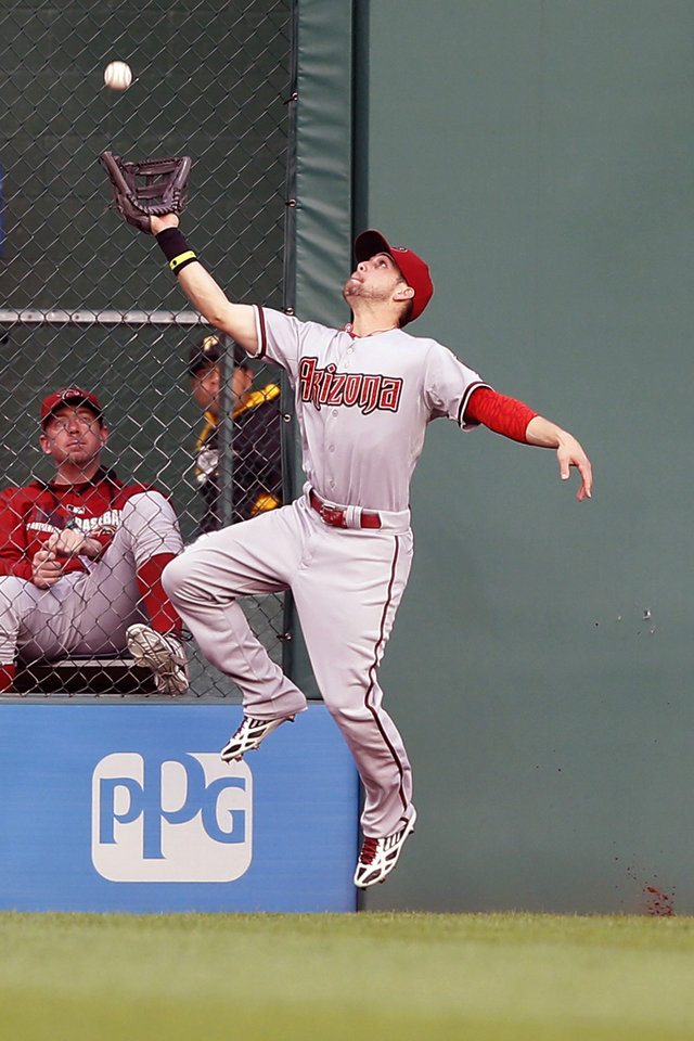Photo - Arizona Diamondbacks center fielder Ender Inciarte jumps to catch a deep fly ball by Pittsburgh Pirates' Andrew McCutchen for the final out of the fourth inning of the baseball game on Tuesday, July 1, 2014, in Pittsburgh. (AP Photo/Keith Srakocic)