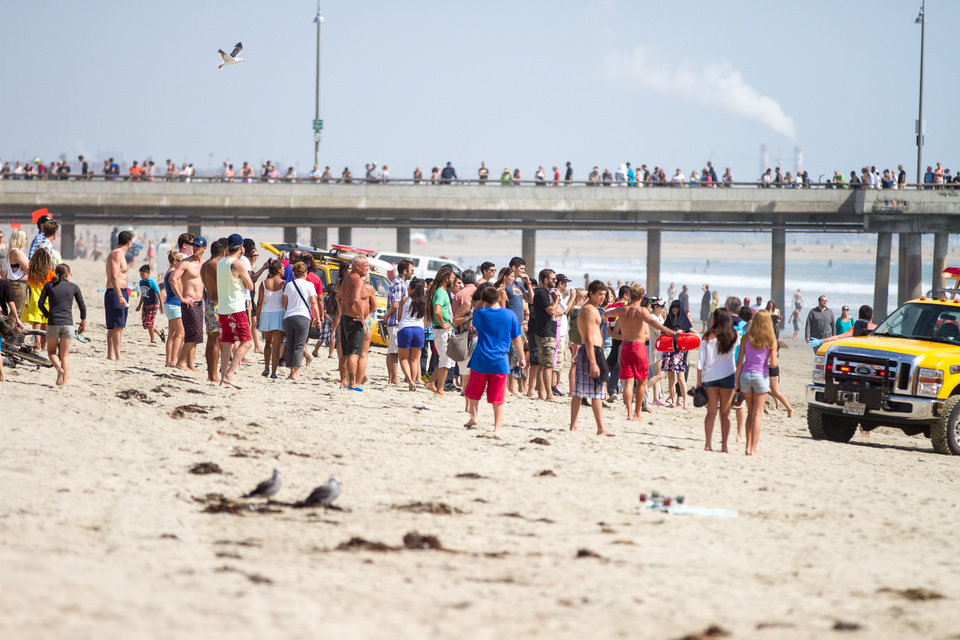 Photo - CORRECTS SPELLING OF LAST NAME: Pedestrians and beachgoers stand on the shore near Venice Beach as lifeguards, right, bring in a swimmer rescued from the water after a lightening strike Sunday July 27, 2014 in Los Angeles. Authorities said lightning struck 14 people, leaving two critically injured, as rare summer thunderstorms swept through Southern California on Sunday. (AP Photo/Steve Christensen)