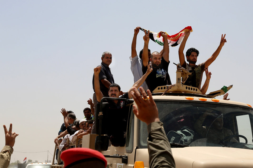 Photo - Iraqi men wave a national flag as they leave the main recruiting center to join the Iraqi army in Baghdad, Iraq, Saturday, June. 14, 2014, after authorities urged Iraqis to help battle insurgents. Hundreds of young Iraqi men gripped by religious and nationalistic fervor streamed into volunteer centers across Baghdad Saturday, answering a call by the country's top Shiite cleric to join the fight against Sunni militants advancing in the north. (AP Photo/Karim Kadim)