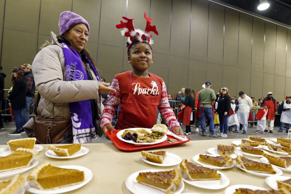 Photo - Volunteer Kendra Lange, 8, from Edmond, helps Oni Xanders gather her Christmas Dinner during the annual Red Andrews Christmas Dinner in the Cox Convention Center on Monday, Dec. 25, 2017 in Oklahoma City, Okla.  Photo by Steve Sisney, The Oklahoman