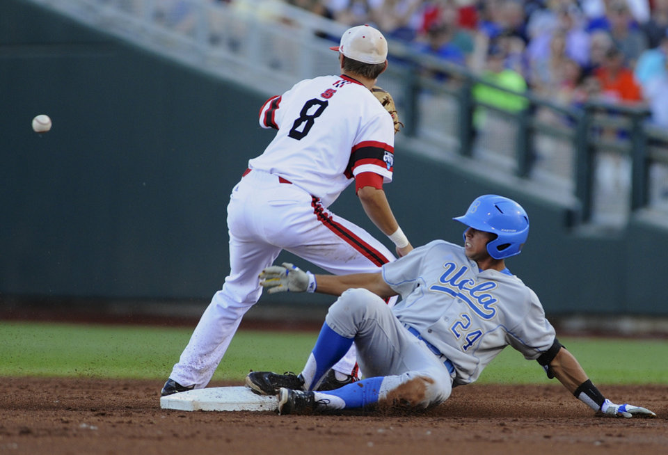 Photo - UCLA's Brian Carroll reaches second base ahead of the throw to North Carolina State shortstop Trea Turner after hitting a double in the second inning of an NCAA College World Series game in Omaha, Neb., Tuesday, June 18, 2013. (AP Photo/Eric Francis)