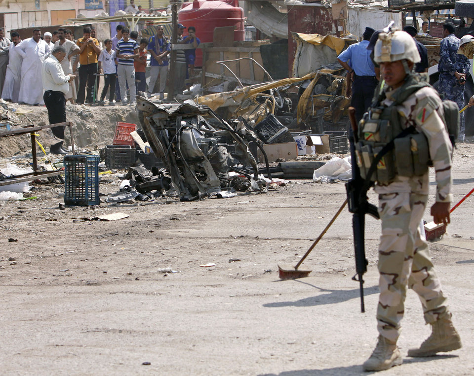 Photo -   An Iraqi soldier stands guard as security forces inspect the scene of a car bomb attack in Basra, 340 miles (550 kilometers) southeast of Baghdad, Iraq, Sunday, Sept. 9, 2012. In violence, which struck at least 10 cities across the nation Insurgents killed at least 39 people in a wave of attacks against Iraqi security forces on Sunday, gunning down soldiers at an army post and bombing police recruits waiting in line to apply for jobs, officials said. (AP Photo/Nabil al-Jurani)