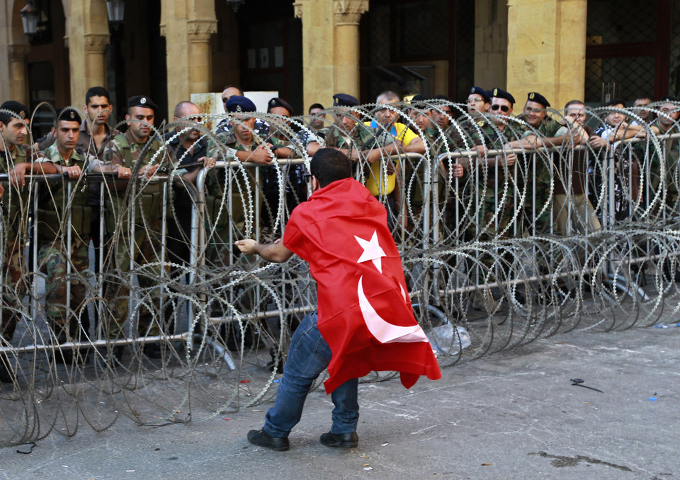 Photo - A civil society protester tries to remove barbed wire while wearing a Turkish flag during a demonstration protesting the extension of parliament's mandate, near Parliament in Beirut, Lebanon, Friday, June 21, 2013. Lebanon's parliament on May 29 extended its term by a year and a half, skipping scheduled elections because of the country's deteriorating security linked to the civil war next door in Syria. (AP Photo/Bilal Hussein)